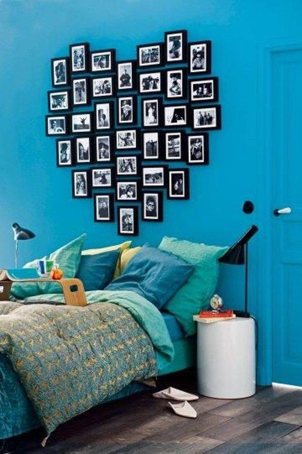 Dormitorio de color turquesa con cabecera en forma de corazón hecha con marcos de imagen